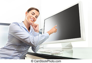 woman in office at desk in front of computer pointing at the screen