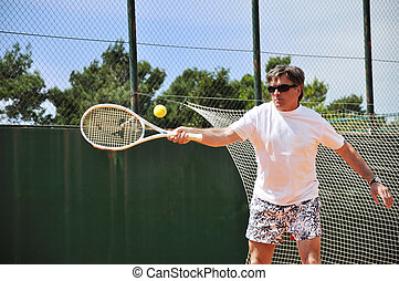 Middle age man playing tennis - Middle age man playing...