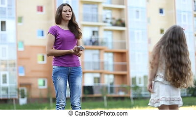 Mother with daughter stand on street