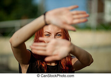 girl closes hands - beautiful red-haired girl closes hands...