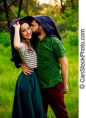 Beautiful pair of lovers hiding from the rain under his...