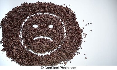 Sad smiley made of coffee beans becoming happy - Sad...