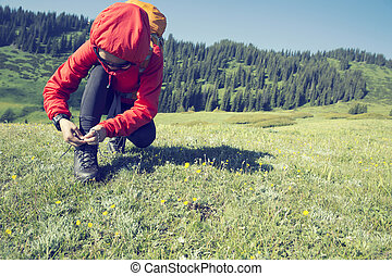 young woman hiker tying shoelace on moutain grassland