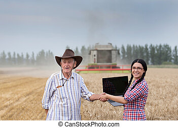 Man and woman shaking hands at harvest - Young businesswoman...