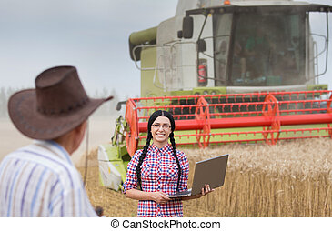 People at harvest - Pretty young woman with laptop standing...