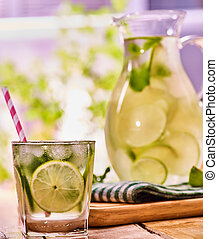 On wooden table is glass jug with transparent drink. -...
