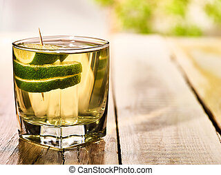 On wooden boards stands glass with alcohol green lime drink...