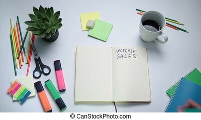 Human hand writing steps to increase sales - Top view of...
