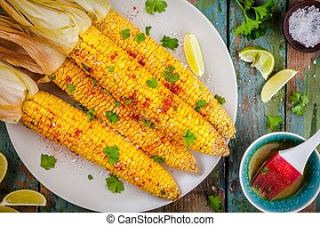 baked sweet corn cobs with herb butter and lime on wooden...