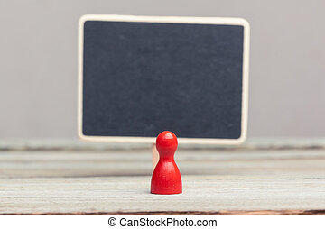 red pawn with empty blackboard - a red pawn in front of a...
