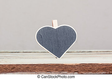 Heart shaped sign on wood table - blank copyspace...