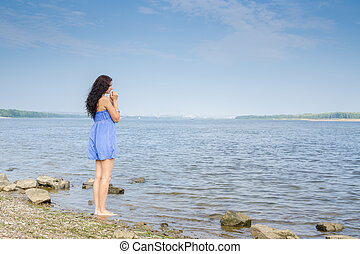 Sad young brunette woman in a blue summer dress standing on...