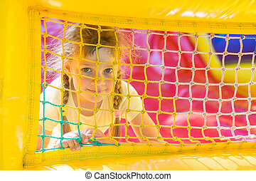 A five-year girl is looking through a mesh trampoline inflatable