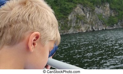 child blowing soap bubbles near the water