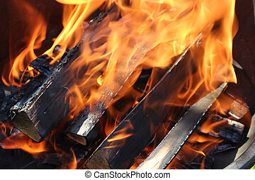 Flames charred and woods - Charred wood and bright flames on...