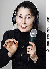 Woman listening to music - Beautiful mature asian woman...