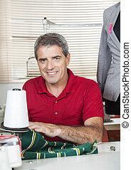 Confident Fashion Designer Working At Workbench - Portrait...