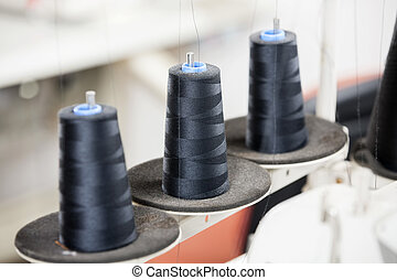 Thread Spools In Factory - Black thread spools at sewing...