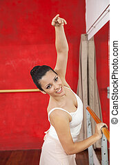 Smiling Dancer Holding Barre While Practicing In Ballet...