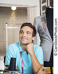 Thoughtful Tailor Smiling While Sitting At Factory -...