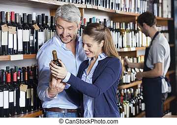 Couple Looking At Wine Bottle In Shop - Happy couple looking...