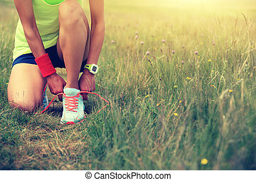 young woman runner tying shoelace on nature trail