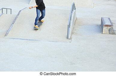 skateboarder legs riding skateboard at skatepark ramp