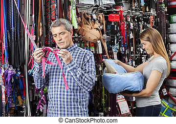 Couple Buying Pet Equipment At Store - Couple examining pet...
