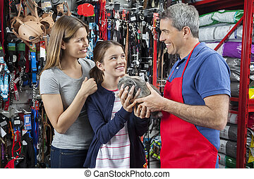 Salesman Giving Rabbit To Girl With Mother At Pet Store -...