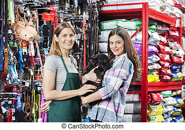 Happy Woman Buying French Bulldog From Saleswoman In Store -...