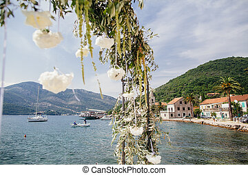 destination wedding arch with flower decoration and sea view...
