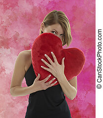 Woman with heart pillow - Young beautiful woman hiding...