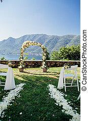 destination wedding arch with flower decoration in...