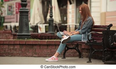 Girl working on a computer in the street and picks up the phone.