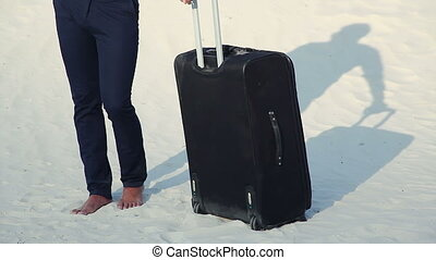 Businessman in desert. A young man in a business suit and a large luggage bag in the desert. Businessman on the road to the resort. White sand. Sultry desert.