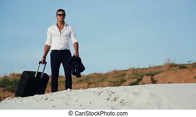 Businessman in desert. A young man in a business suit and a large luggage bag in the desert.