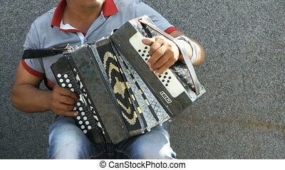 A man playing accordion in summer outdoors