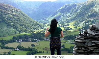 Woman on mountain taking picture