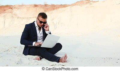 Businessman in the desert is working with a laptop and...