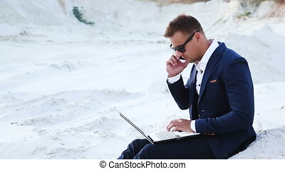 Businessman in the desert is working with a laptop and talking on a cell phone. Young man in sunglasses and a business suit.