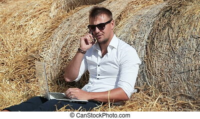 Business man looks beautiful works with a laptop and talking...