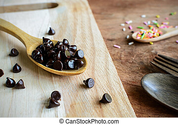 Chocolate chips on wooden spoon and ingredients for cooking dessert