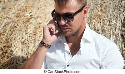 Business man looks beautiful works with a laptop and talking on the phone sitting in a haystack.