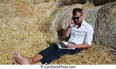 Business man looks beautiful works with a laptop and talking on the phone sitting in a haystack. Summer holidays in the countryside. Work from anywhere. Freelance at work.