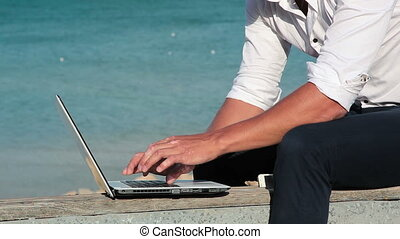 Business man in white shirt and sunglasses with a laptop at the seashore.