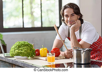 Guy is anticipation of self-made dish - Joyful young man is...