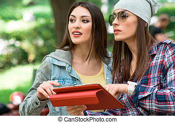 Cheerful female friend use modern gadget in nature - Two...