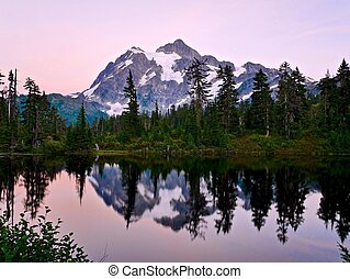 Reflection of mountain in calm water at sunset. - Picture...