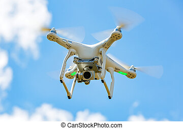 Flying drone with camera against the sky