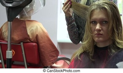 woman before mirror in hairdresser parlour. 4K - young woman...